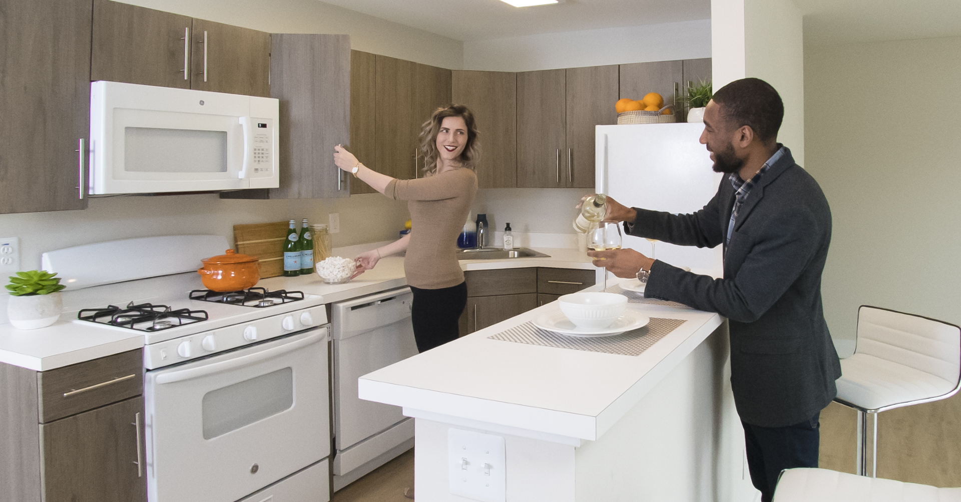 two residents pouring wine in an updated kitchen at apartments in Newark, DE