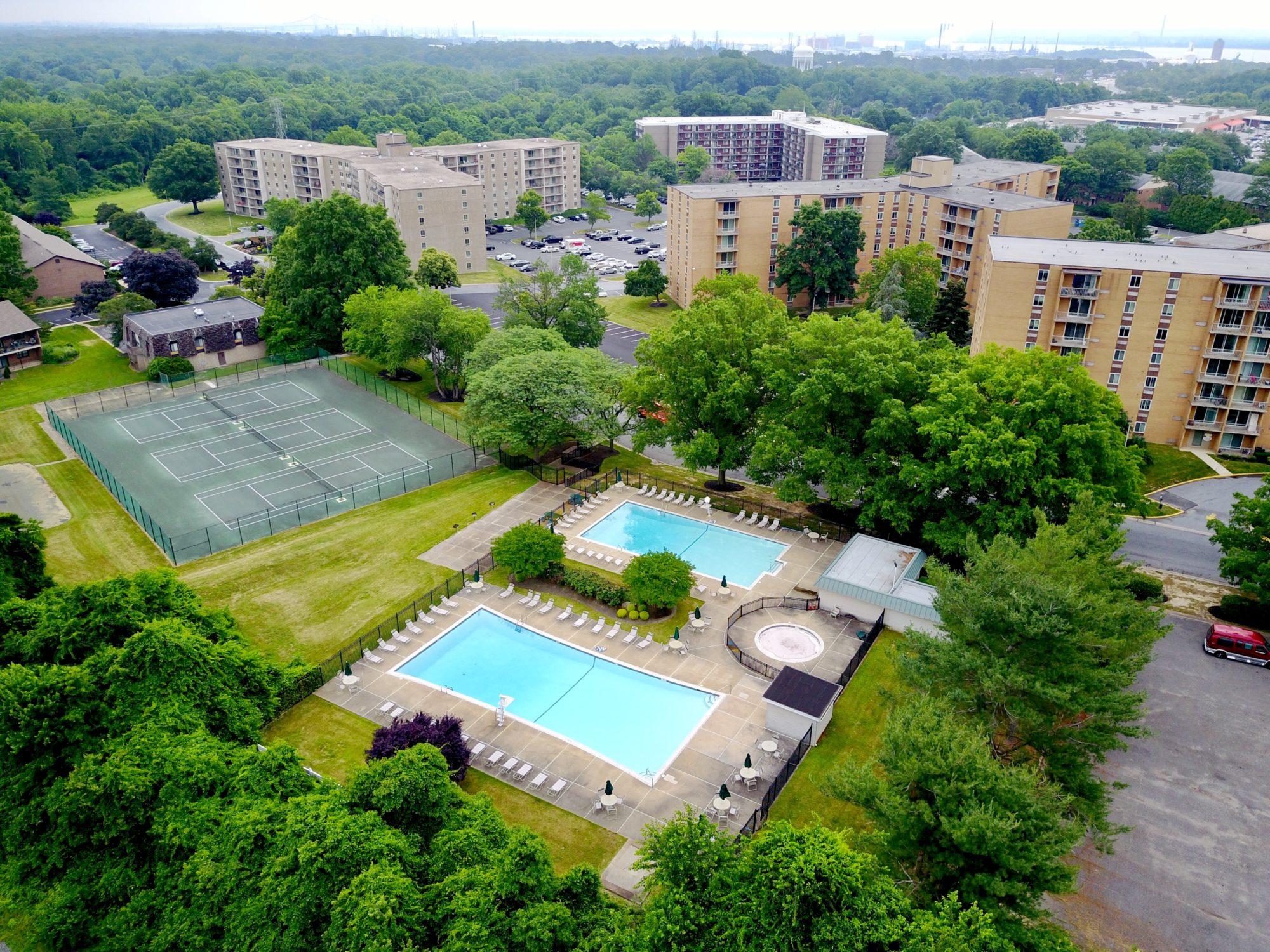 bird's-eye-view of two swimming pools, tennis courts and high-rise buildings at the Whitney Apartments in Claymont DE