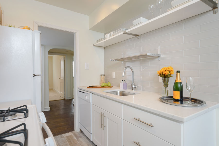 white kitchen with cabinet, shelf space and gas range stove in the Canterbury Apartments in Mt. Airy