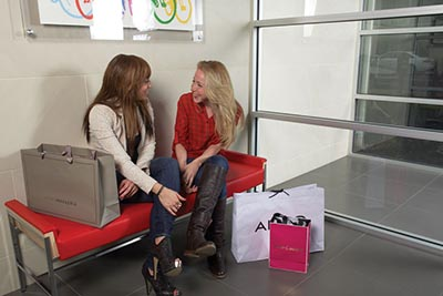 Two girls sitting on a red bench in our lobby at our Roxborough apartments - Ridge Court - Galman Group