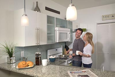 A couple laughing in the kitchen with granite countertops and white finished appliances in our Roxborough Philadelphia apartments - Ridge Court - Galman Group