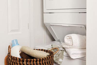 Stacked washer and dryer with laundry basket in our Roxborugh apartments in Philadelphia - Ridge Court - Galman Group