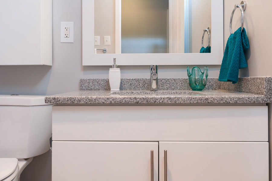 close up of a white sink and cabinet of the bathroom in a Claymont DE apartment at Whitney Apartments