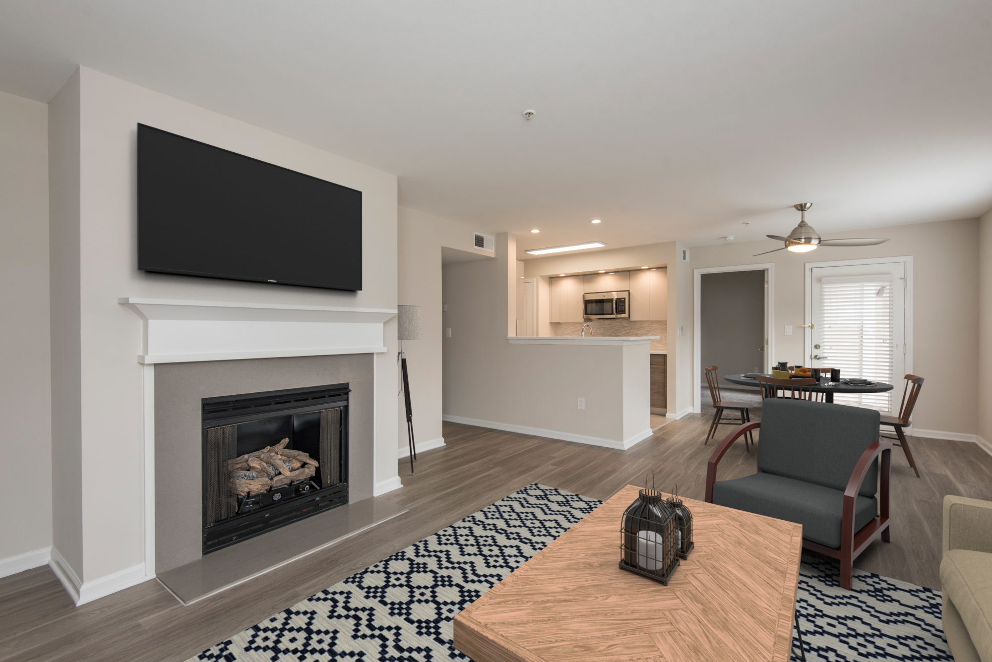 apartment living room with gas fireplace looking toward a spacious kitchen and eat-in area at Edge of Yardley