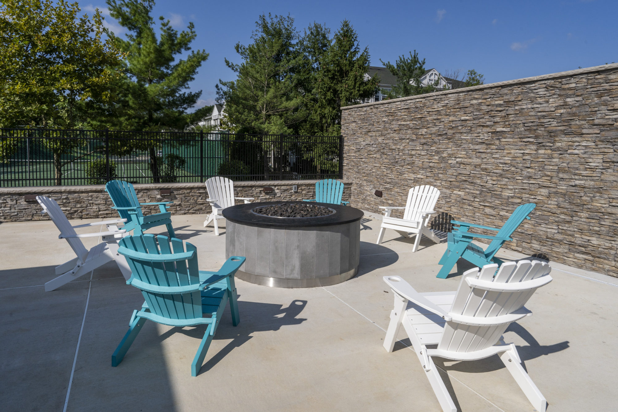 fire pit surrounded by adirondack chairs in the outdoor space at Edge of Yardley apartments