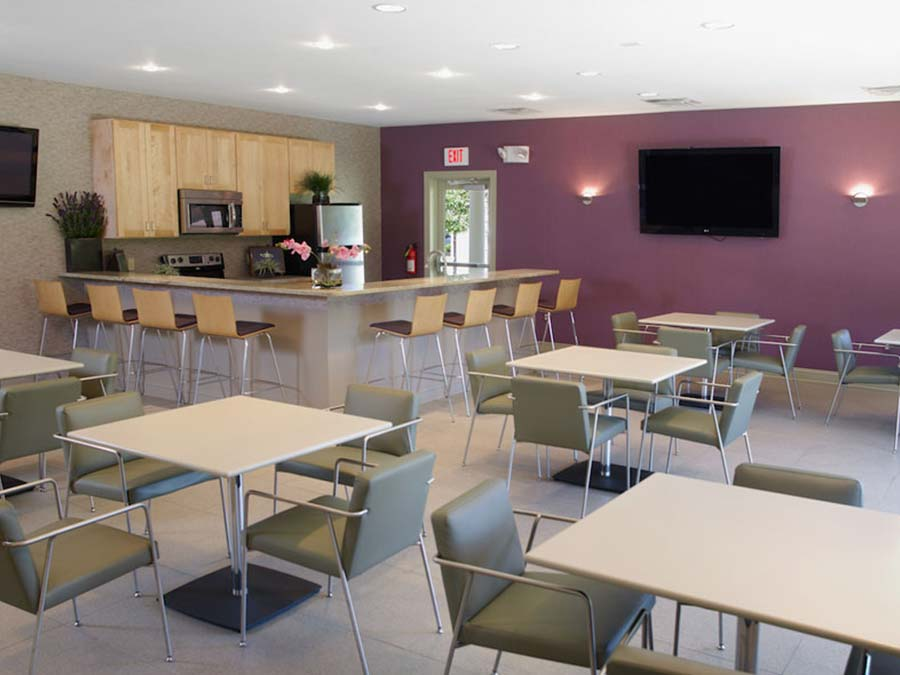 Castlebrook Apartments in New Castle DE has a community clubhouse featuring a café with several tables and bar stools