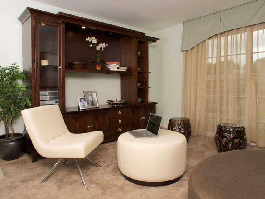 modern white furniture and bookshelf in a living room with wall-to-wall carpeting at Castlebrook Apartments in New Castle DE