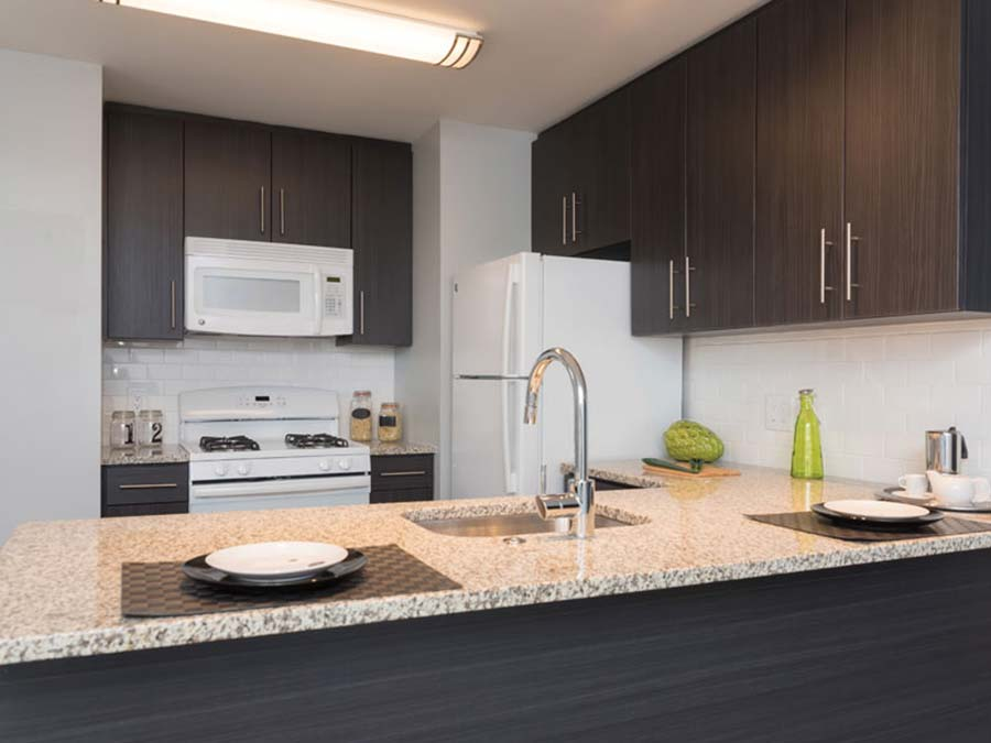 kitchen with white appliances and wooden cabinets in Donna Court apartments