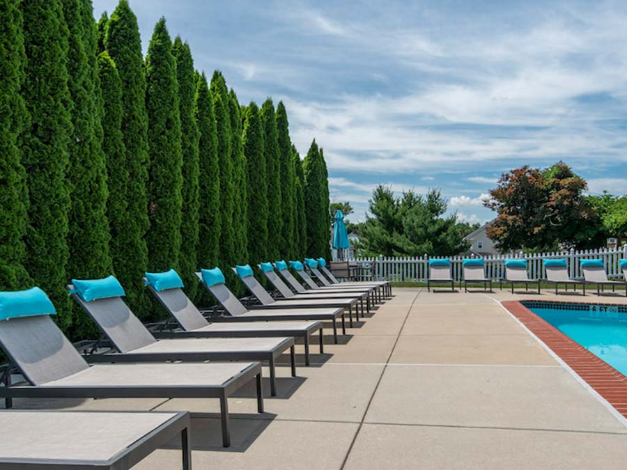 lounge chairs around a swimming pool at an apartment in Reading PA
