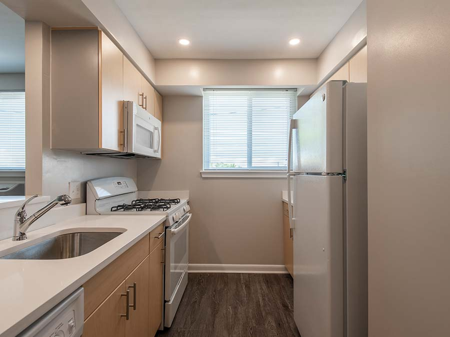 Gail Court Apartments galley kitchen with white appliances