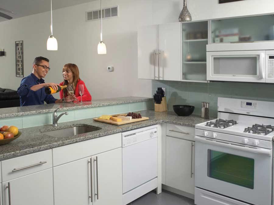 Ridge Court couple enjoying a bottle of wine in the kitchen