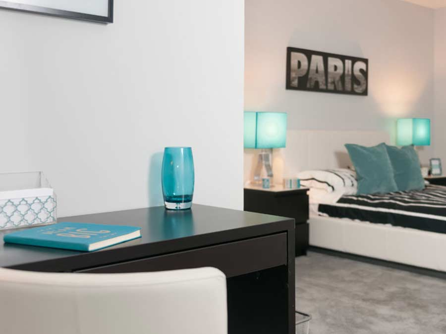 a bedroom decorated in a playful aqua and white color palate for a New Castle DE apartment