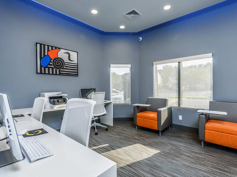 Sophias Place East business center decorated in a modern grey and orange color palate offers computer stations, printers and high speed internet