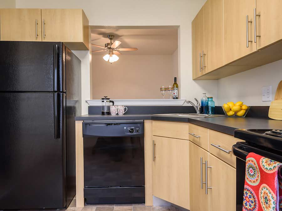 updated kitchen with black appliances and wooden cabinets in an apartment in New Castle DE