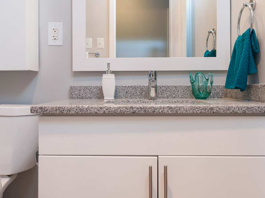 close up of a white sink and cabinet of a bathroom in a Claymont DE apartment at Whitney apartments