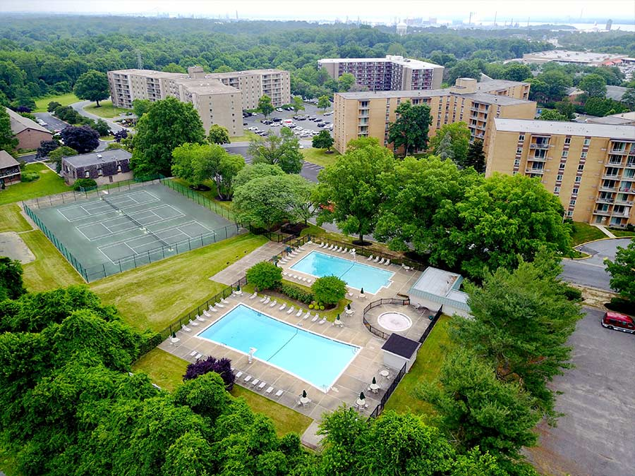 bird's eye view of two swimming pools, tennis courts, and high-rise buildings at Whitney Apartments in Claymont DE
