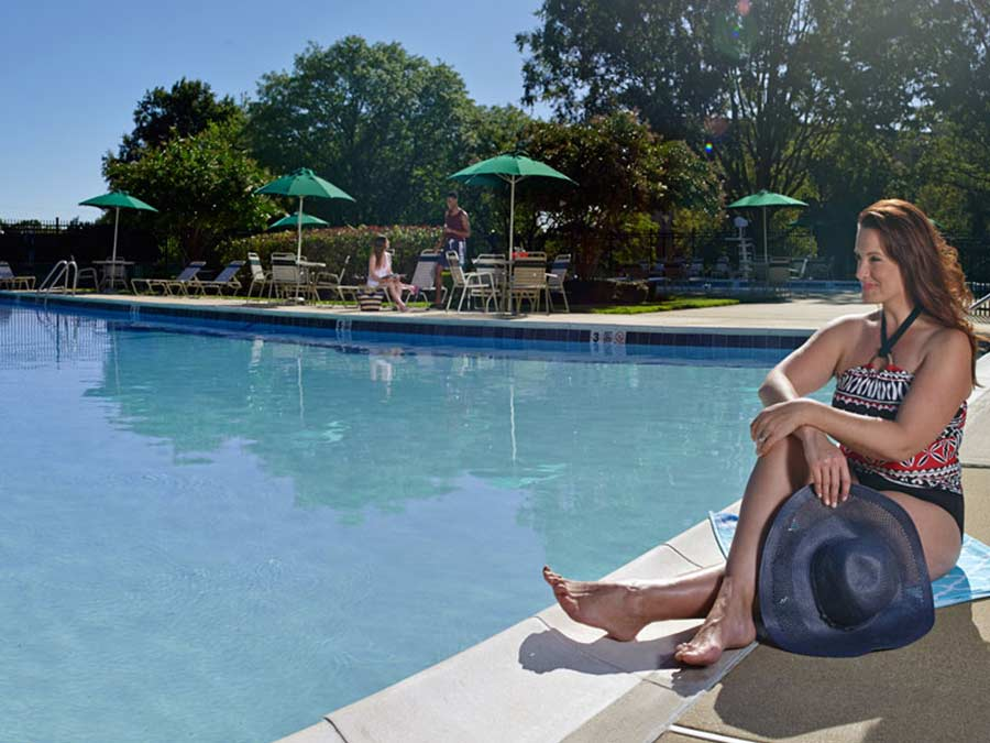 woman sits by the swimming pool at the Whitney Apartments in Claymont DE