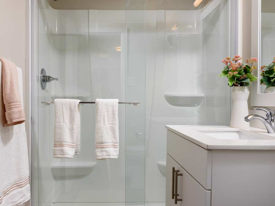 Algon Flats bathroom with sliding glass door shower with multiple shelves
