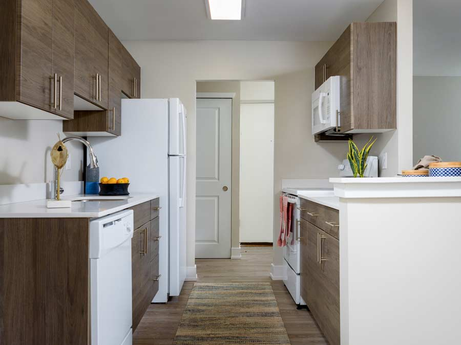 Algon Flats kitchen with new cabinetry and white appliances